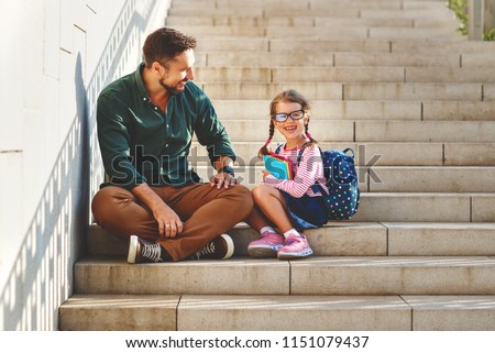 first day at school. father leads a little child school girl in first grade #1151079437