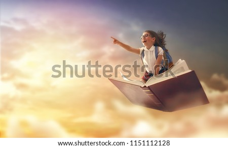 Back to school! Happy cute industrious child flying on the book on background of sunset sky. Concept of education and reading. The development of the imagination. #1151112128