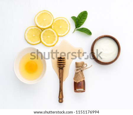 Top view of egg,yogurt,honey and lemon on white background in concept simple homemade hair mask.Natural hair care recipe with essential oils.Best natural hair care for long, strong and beautiful hair. #1151176994