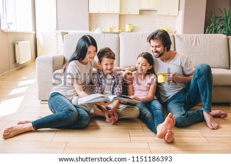 People are sitting on the floor. Boy has book. He reads it with sister and mom. Guy has a cup and look at book. He smiles. #1151186393