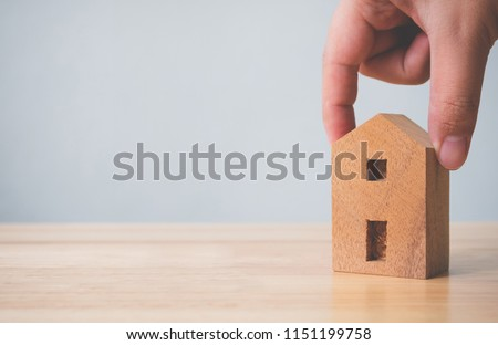 Property investment real estate and house mortgage financial concept. Hand holding wooden home on table #1151199758