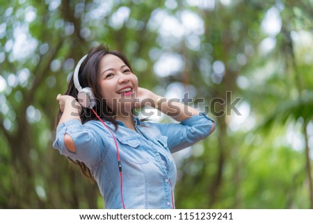 Young beautiful woman enjoying music in the garden listening to music with headphones. #1151239241