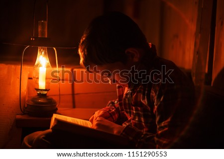 boy reading in the light of an old lamp. the child sitting on a dark staircase with a book #1151290553