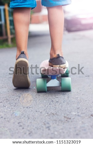 The boy child legs on skateboard going down the sidewalk, vertical, toned photo #1151323019