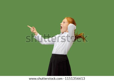 Wow. Beautiful female half-length front portrait isolated on green studio backgroud. Young emotional surprised teen girl standing with open mouth. Human emotions, facial expression concept. Trendy #1151356613