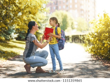 Parent and pupil of primary school go hand in hand. Woman and girl with backpack behind the back. Beginning of lessons. First day of fall. #1151359865
