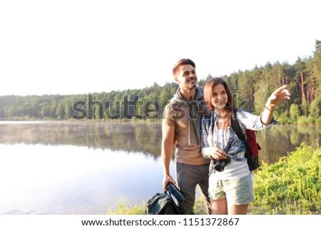 Young couple on shore of beautiful lake. Camping season #1151372867