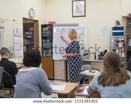 The teacher in the class draws on the board. Beauty industry, training hairdressers. Russia. Saint-Petersburg. August 2018 #1151385302