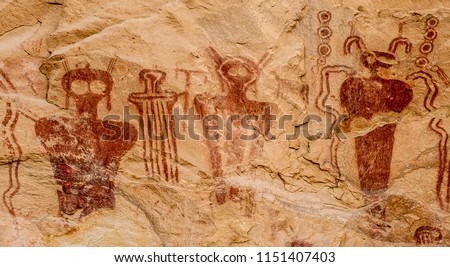"""Ancestral Puebloan or Anasazi pictographs of strange anthropomorph figures, often referred to as """"ancient aliens"""" on the wall of Sego Canyon in Thompson Springs, Utah.   Royalty-Free Stock Photo #1151407403"""