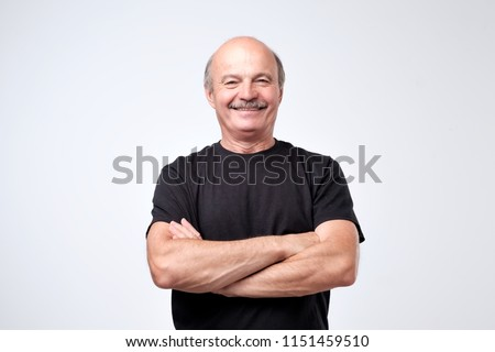 Charming handsome senior man in casual clothes keeping arms crossed and smiling while standing isolated on white background. Positive facial emotion #1151459510