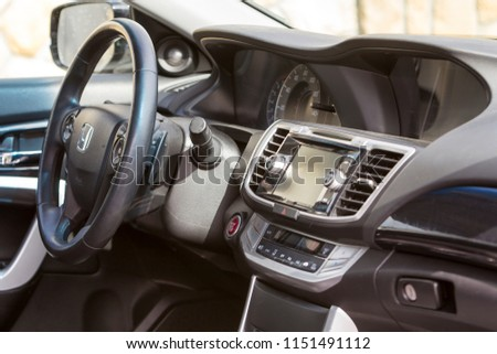 KYIV, UKRAINE - July 9, 2018: Close-up of luxurious car interior details. Side view mirror, dashboard and steering wheel. Transportation, design, modern technology, comfortable lifestyle concept. #1151491112