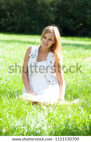 Young beautiful blonde woman in white dress sitting on green grass in the summer park #1151530700