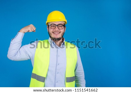 Young engineer raising his arm showing the biceps with a smiley face emotion, on a blue background. #1151541662