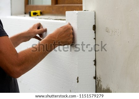 Worker hands installing white rigid polyurethane foam sheet on plastered brick wall. Modern technology, renovation, insulation concept. #1151579279