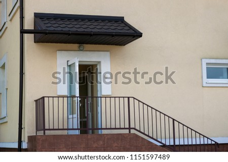Close-up outdoors detail of new kindergarten or school building with beige stucco walls, open white entrance door and metal protective simple primitive brown metal staircase fence and handrails. #1151597489