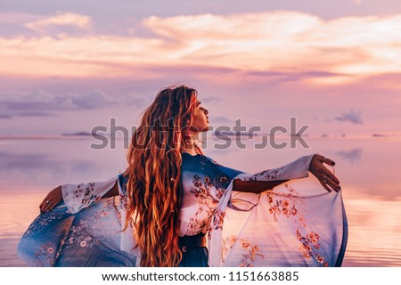 beautiful young woman in elegant dress on the beach at sunset Royalty-Free Stock Photo #1151663885