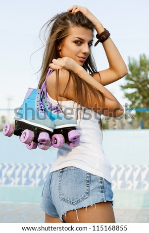 Photograph of a roller derby sexy woman holding her skates by the laces, outdoors #115168855
