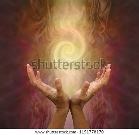 Channeling Golden Vortex healing energy  - female hands held open and palms upwards with a vortex energy formation above on a warm golden brown background  #1151778170