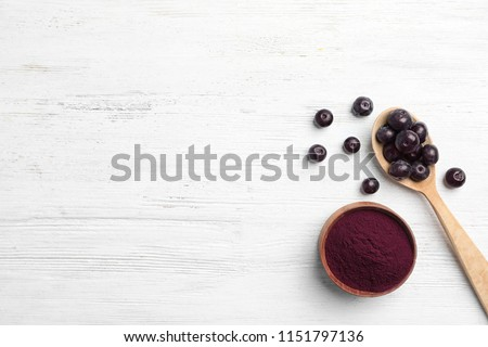 Bowl of acai powder and fresh berries on light wooden table, flat lay with space for text #1151797136