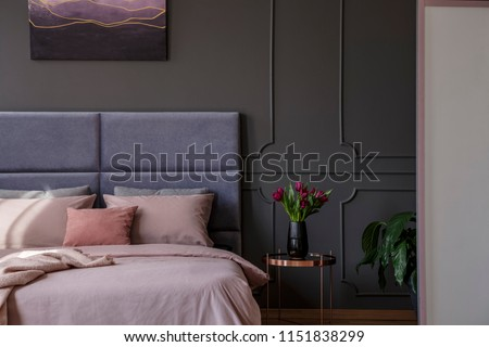 Sophisticated pastel bedroom interior with tulips next to bed against grey wall with molding and poster #1151838299