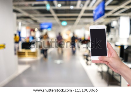 Hands holding mobile phone with shopping mall or department store  blurred background and bokeh light #1151903066