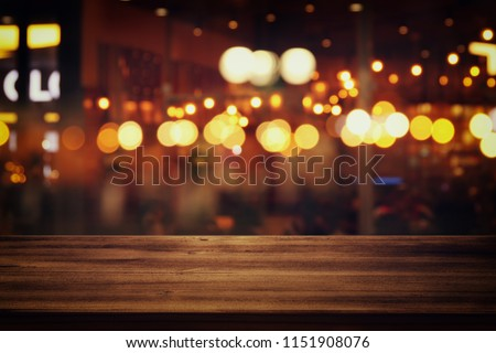 Image of wooden table in front of abstract blurred restaurant lights background #1151908076