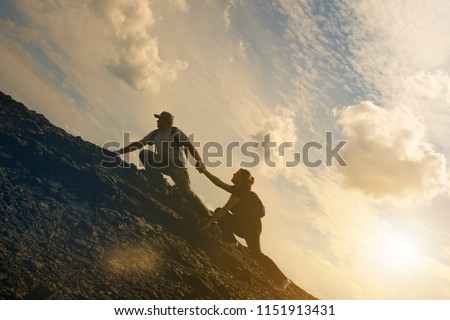 The joint work teamwork of two people man and girl travelers help each other on top of a mountain climbing team, a beautiful sunset landscape. The silhouettes on top of a mountain #1151913431
