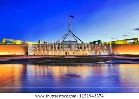 Facade of new parliament house in Canberra on capitol hill at sunset with bright illumination reflecting in blurred waters of pool. Public building free for admission by australians and guests. #1151943374