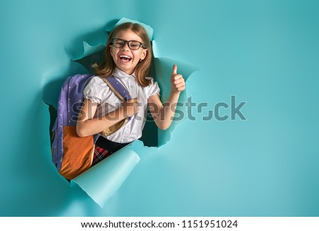 Back to school and happy time! Cute industrious child is breaking through color paper wall. Kid with backpack. Girl ready to study. #1151951024