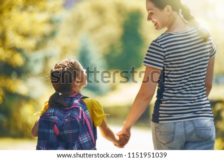 Parent and pupil of primary school go hand in hand. Woman and girl with backpack behind the back. Beginning of lessons. First day of fall. #1151951039