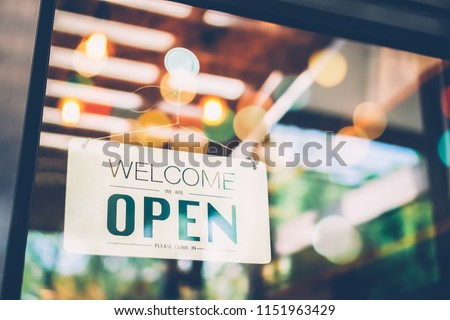 """Business coffee cafe shop sign board is hang on door and show """"Welocome We are open"""" with cafe and resturant blur bokeh background."""