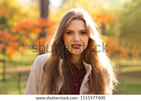 Portrait of smiling woman in autumn park #1151977400