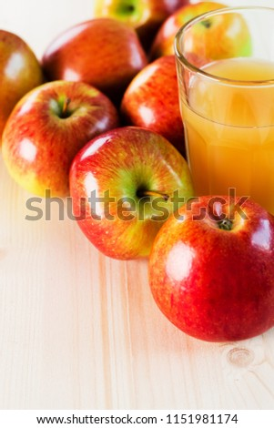 Glass of fresh apple cider near autumn apples. Wooden background, top view, space for text. #1151981174