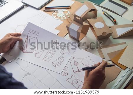 Designer sketching drawing design Brown craft cardboard paper product eco packaging mockup box development template package branding Label . designer studio concept . Royalty-Free Stock Photo #1151989379