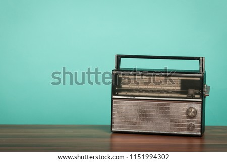 Old radio on table in front of green background. Vintage style photo #1151994302