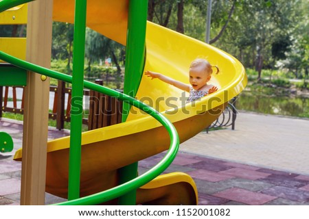 Two year cute blonde girl sliding on yellow slide at playground