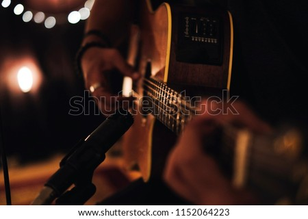 A man playing acoustic guitar in recording session with microphone and beautiful lighting