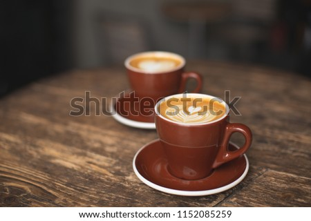 Two beautiful burgundy cups of cappuccino with trendy heart shape latte art. Summer loft cafe background. Urban space. Drinking coffee on the terrace. #1152085259