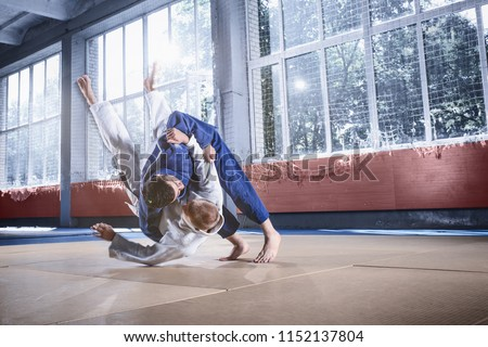 Two judo fighters showing technical skill while practicing martial arts in a fight club. The two fit men in uniform. fight, karate, training, arts, athlete, competition concept Royalty-Free Stock Photo #1152137804