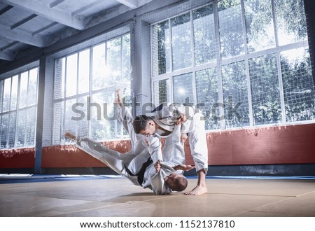 Two judo fighters showing technical skill while practicing martial arts in a fight club. The two fit men in uniform. fight, karate, training, arts, athlete, competition concept Royalty-Free Stock Photo #1152137810