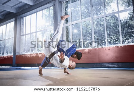 Two judo fighters showing technical skill while practicing martial arts in a fight club. The two fit men in uniform. fight, karate, training, arts, athlete, competition concept Royalty-Free Stock Photo #1152137876