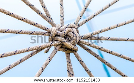 lots of ropes and a big knot against the blue sky Royalty-Free Stock Photo #1152151433