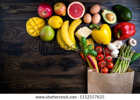 Healthy food background. Healthy food in paper bag vegetables, fruits, pasta, eggs, cheese and mushrooms on dark. Shopping food supermarket concept. Vegetarian food. Top view. Copy space #1152157625