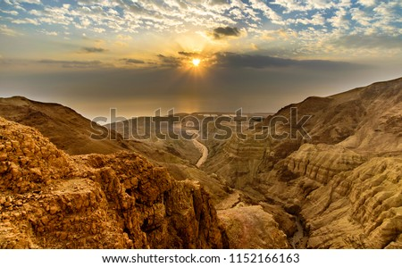 Beautiful landscape of Israeli Judean Desert mountains, with sunrise over the dry riverbed of Nahal Dragot Wadi, popular hiking trail winding between rugged rocky cliffs towards the Dead Sea #1152166163