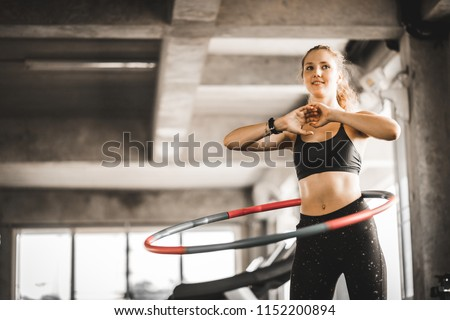 Beautiful caucasian young woman doing hula hoop in step waist hooping forward stance. Young woman doing hula hoop during an exercise class in a gym. Healthy sports lifestyle, Fitness, Healthy concept. Royalty-Free Stock Photo #1152200894