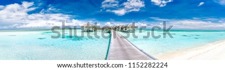 Panoramic landscape of Maldives beach. Tropical panorama, luxury water villa resort with wooden pier or jetty. Luxury travel destination background for summer holiday and vacation concept. #1152282224