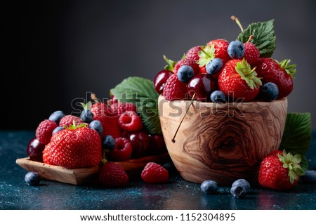 Berries closeup colorful assorted mix of strawberry, blueberry, raspberry and sweet cherry in studio on dark background. Royalty-Free Stock Photo #1152304895