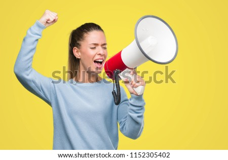 Beautiful young woman holding megaphone annoyed and frustrated shouting with anger, crazy and yelling with raised hand, anger concept #1152305402