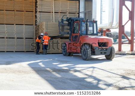 workers load pine boards on sawmill using orange loader  #1152313286