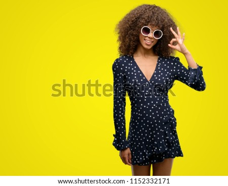 African american woman with sunglasses and summer dress doing ok sign with fingers, excellent symbol #1152332171